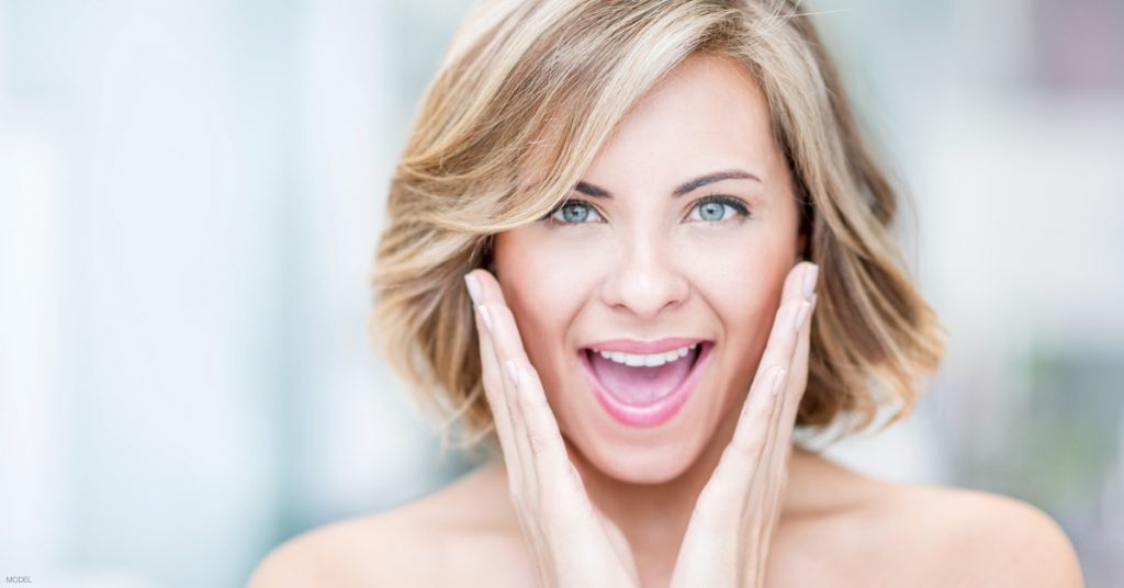 Smiling woman with hands in a V shape on either side of face